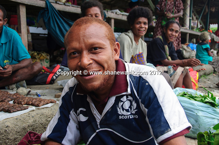 A local tobacco seller at Alotau market seems to have some Scottish heritage with red hair and a Scottish rugby jersey on.