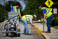 NWA Democrat-Gazette/JASON IVESTER<br /> Eric Casson (from left), Angel Cruz and Matthew Henson apply a fresh coat of paint Tuesday, June 13, 2017, to the curb along W. Johnson Avenue in Springdale. The Springdale Public Works crew were repainting the curbs on the streets between and including Johnson and Emma Avenues.