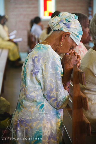 Elderly lady praying at the Creole mass in Paramin Catholic church