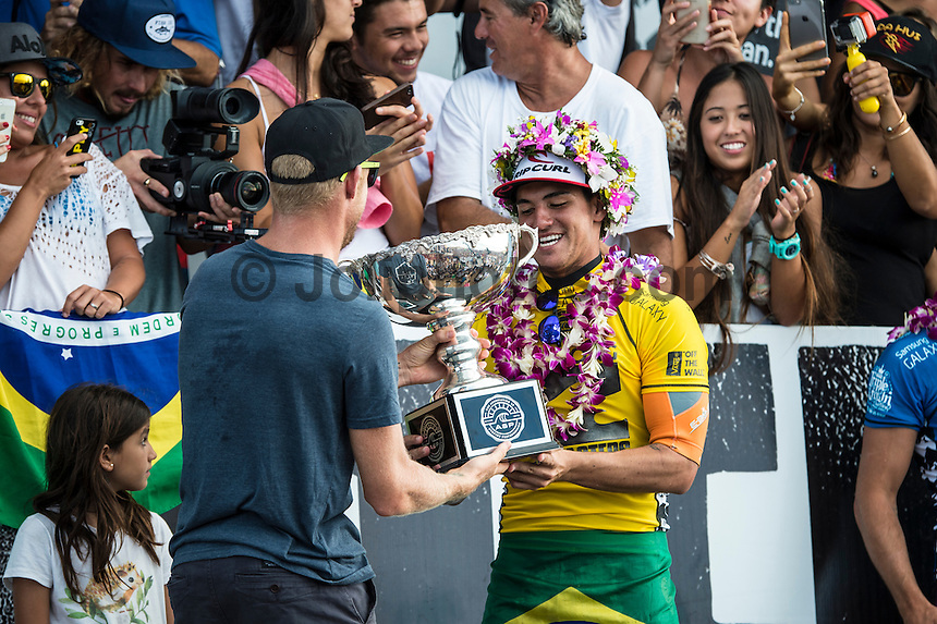 Pipeline, North Shore of Oahu, Hawaii Friday December 19 2014) Defending World Champion Mick Fanning (AUS) hands over the world title trophy to World Champion elct Gabriel Medina (BRA).- The final stop of the 2014  World Championship Tour, the Billabong Pipe Masters in Memory of Andy Irons, was  ccompleted today in NW double overhead surf. <br /> Gabriel Medina (BRA) became the first ever Brazilian World Champion after both rival contenders , Kelly Slater (USA) and Mick Fanning (AUS) were eliminated from the contest. Medina went onto finish 2nd overall behind Julian Wilson (AUS). <br /> In the overlapping heat format Wilson surf three consequent heats and still had enough entry to take out the 30 minute final.<br /> By winning the final Wilson also won the covered Vans Triple Crown of Surfing for best overall performance through the whole Triple Crown.<br /> <br /> The Billabong Pipe Masters in Memory of Andy Irons will determine this year&rsquo;s world surfing champion as well as those who qualify for the elite tour in 2015. As the third and final stop on the Vans Triple Crown of Surfing Series  the event will also determine the winner of the revered three-event leg.<br /> <br />  Photo: joliphotos.com
