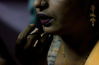 Hajra, puts on her make-up in preparation for the evenings clients. She is HIV positive, but still has to work as she cannot afford to live without the money she earns from sex work.