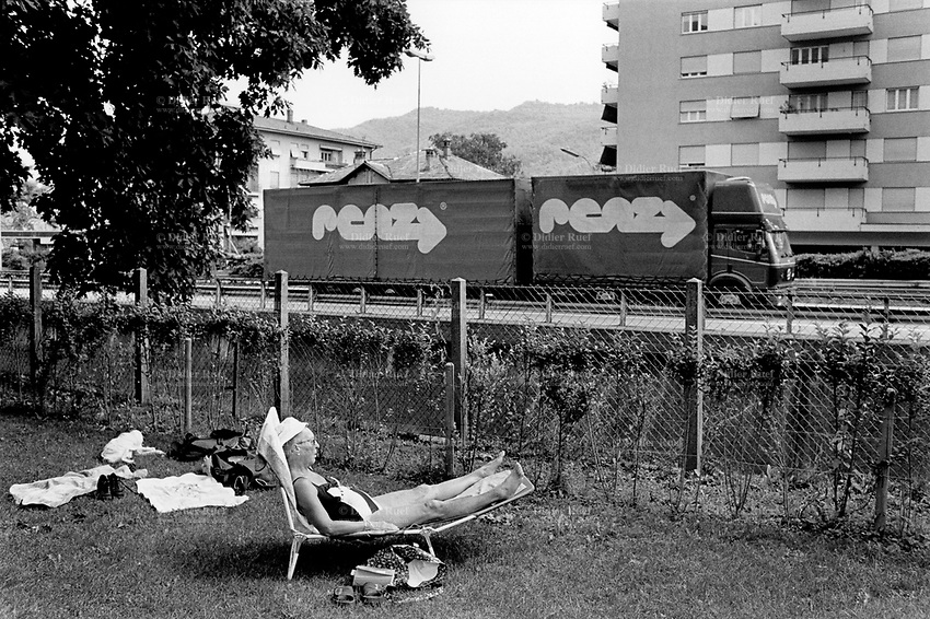 Switzerland. Chiasso. An old woman lays down and sleeps under the sun on a chaise longue in the garden of the public swimming pool.  A truck passes by on the highway. © 1998 Didier Ruef
