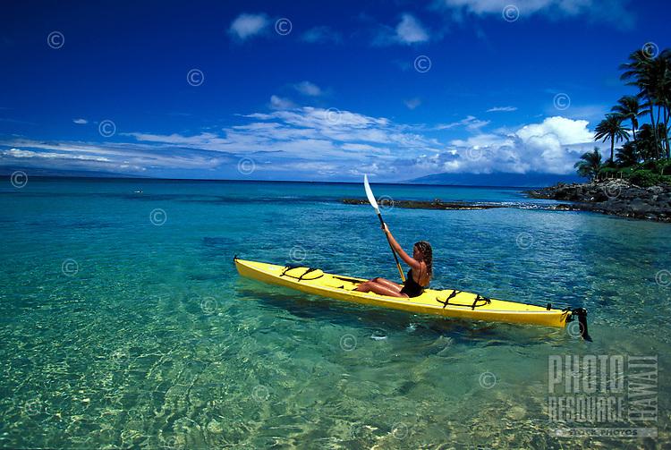 Girl paddles yellow kayak through clear water at Napili Bay, Maui.
