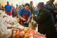 """Volunteers distribute turkeys, stuffing and all the other """"fixin's"""" for a Thanksgiving dinner, to the neediest at the Catholic Charities' Lt. Joseph P. Kennedy Center in Harlem in New York on Tuesday, November 22, 2011. The families, who would otherwise not be able to afford the dinner, received the donations during a time where sources of relief for the poor and unemployed are constrained if not terminated. The food is from the generosity of the former baseball player Rusty Staub and the Urso Fund for the Hungry and Homeless. (© Richard B. Levine)."""