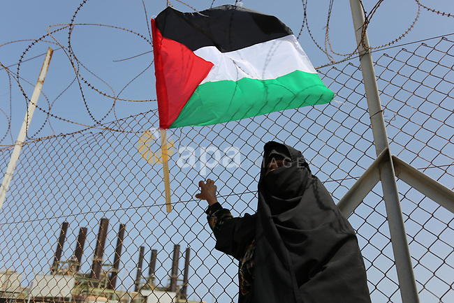 A Palestinian woman stands by a fence during a protest calling for an end to the power crisis, outside the power plant in the central Gaza Strip April 23, 2017. Photo by Ashraf Amra
