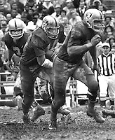 Oakland Raiders Daryle Lamonica hands off to Marv Hubbard led by Charlie Smith around in the mud. (1970 photo/Ron Riesterer)