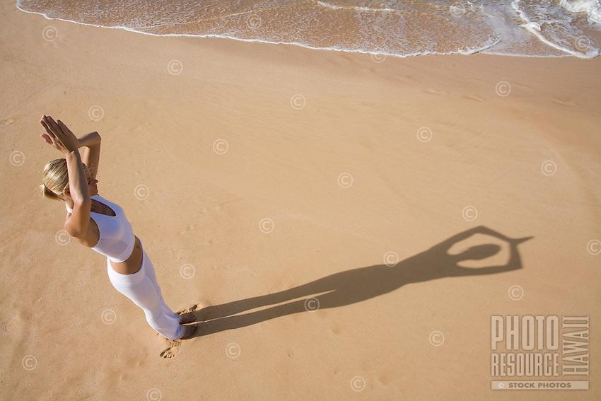 A woman doing yoga on the beach at Makena, Maui.