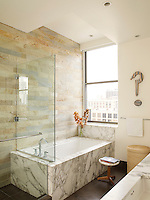 A wall in the master bath is sheathed in Italian quartzite and the bath tub has Kohler fittings. The question mark artwork is by Richard Artschwager