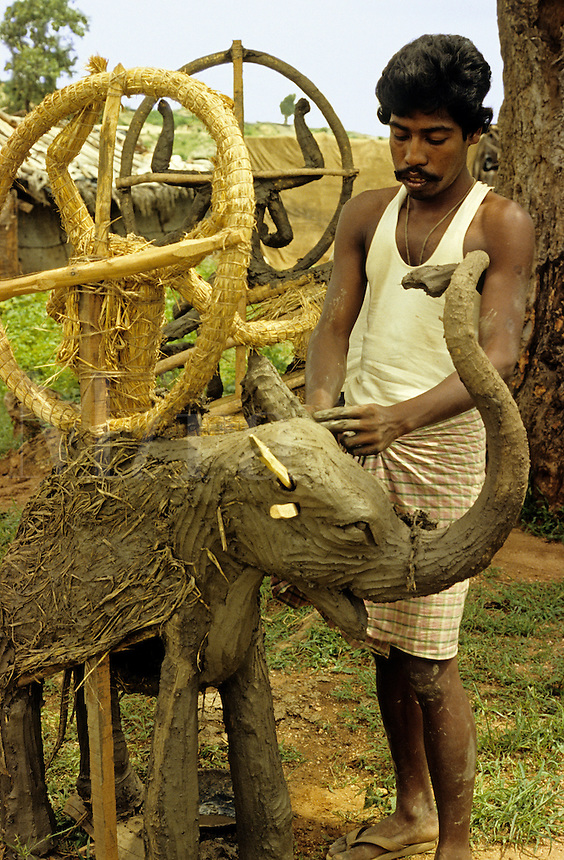 India. Uttar Pradesh. Rihand. Man making clay and straw puja offerings for Hindu ceremonies..