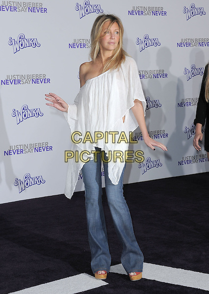 "HEATHER LOCKLEAR .attending the Paramount Pictures' L.A. Premiere of ""Justin Bieber: Never Say Never"" held at The Nokia Theater Live in Los Angeles, California, USA,.February 8th 2011..full length white off the shoulder top poncho jeans wide leg flares platform open toe shoes                                            .CAP/RKE/DVS.©DVS/RockinExposures/Capital Pictures."