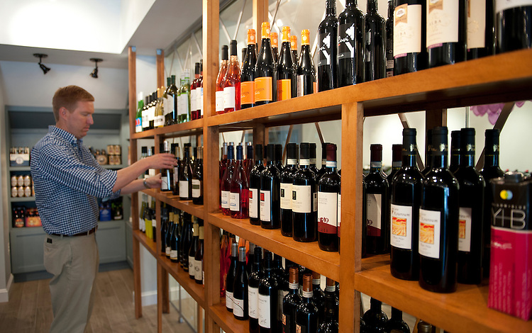 UNITED STATES - July 14: Owner Michael Warner, stocks shelfs at he new wine boutique, DCanter which is opening this week and is located at 545 8th Street, S.E. in Washington, D.C.  (Photo By Douglas Graham/CQ Roll Call)
