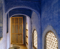 The distressed blue walls of a narrow corridor with trelliswork windows
