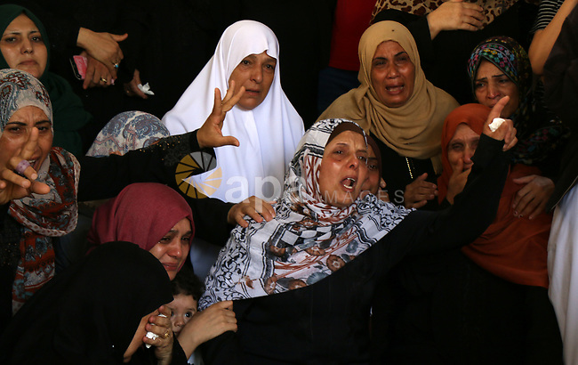 Relatives of Palestinian Mohammed Abu Namous, one of three armed Palestinians killed overnight in Israeli fire along the border with the Gaza Strip, mourn during his funeral in Beit Lahya in northern Gaza strip on August 18, 2019. Israeli forces last night killed three Palestinians and injured a fourth one in an artillery attack near the town of Beit Lahia, north of the Gaza Strip, according to the Ministry of Health. Photo by Mariam Dagga