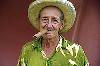 A jovial man enjoys a large Cuban cigar