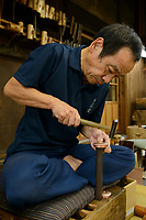 "A ""tsuiki"" copperware artisan hammering a lid for a copper kettle. Gyokusendo, Tsubame, Niigata Pref, Japan, August 24, 2017. Traditional copper metalworking company Gyokusendo was founded in 1816 and is a registered as a traditional craft of Japan. At Gyokusendo, in a highly-skilled craft process, complex items such as teapots are beaten from a single sheet of copper using hammers and hundreds of other specialist tools."