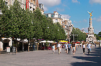 A pedestrian street (rue drouet-d'erion) with people walking in the sunshine on the stone pavement and a big statue with a golden angel on top in the background, Reims, Champagne, Marne, Ardennes, France