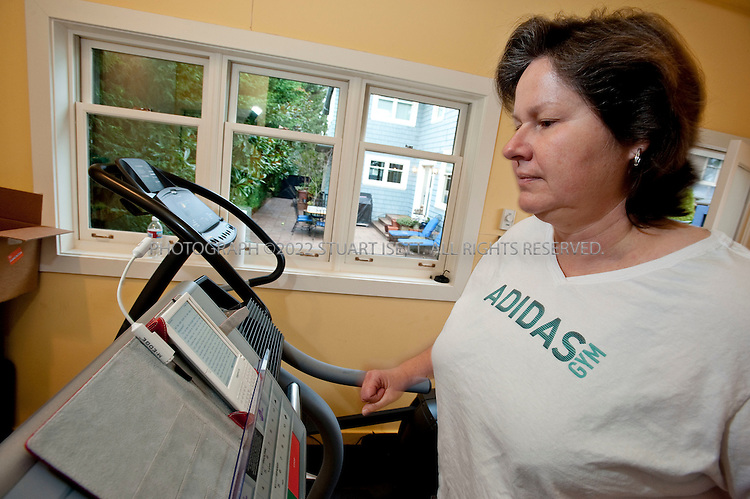 1/7/2010--Seattle, WA, USA..Tina Podlodowski, 49, reading a novel on her Amazon Kindle while on the treadmill in her home in the Queen Anne neighborhood of Seattle...Most people know that listening to music with a good beat can help enhance a workout, and when it comes to other ways to occupy the mind -- like watching television, listening to a podcast or talking to a friend -- there can be benefits too. Trainers say just about anything that gets someone to exercise is beneficial. To go beyond recreational athletics however, you may need to put away the distractions and develop your own internal methods of dealing with the fatigue, discomfort or boredom of your exercise regimen...©2010 Stuart Isett. All rights reserved.