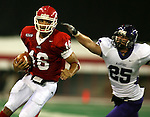 University of South Dakota's Noah Shepard (16) scrambles for a first down as Winona State's Brent Yule reaches for him in the second quarter Saturday night at the DakotaDome. (Photo by Dave Eggen/Inertia)