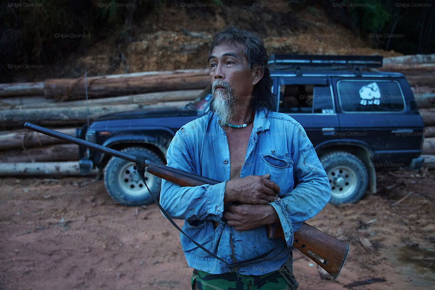 Kelabit man with gun and fourwheel drive vehicle. Sedentary Dayaks, living in longhouses, they rely on fishing, hunting and farming to survive. Limbang, Sarawak, Malaysia 2015<br />