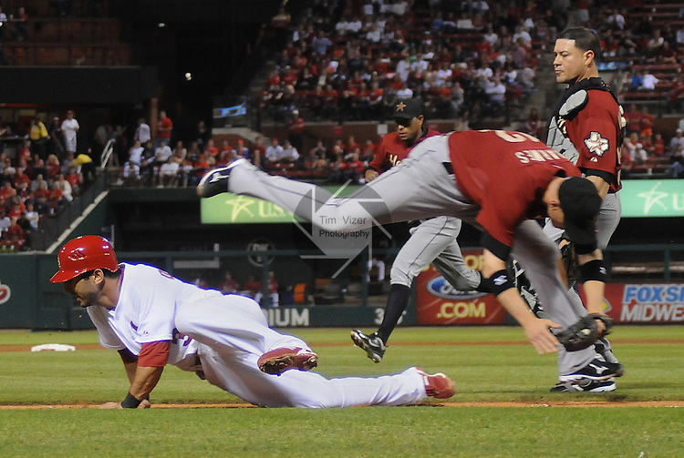 18 May 2011                             St. Louis Cardinals third baseman Daniel Descalso (33, left) got caught in a rundown between third base and home plate as he tried to steal home in the bottom of the fourth inning.  Descalso was tagged out by Houston Astros shortstop Clint Barmes (12), shown here at right flying through the air over Descalso.  In background at right is Houston Astros catcher Humberto Quintero (55) who was also in on the play. The St. Louis Cardinals defeated the Houston Astros 5-1 on Wednesday May 18, 2011 in the first game of a two-game series at Busch Stadium in downtown St. Louis.