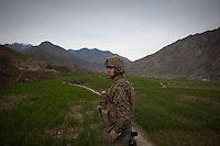 A marine patrols in Nishigham village in Nuristan. The day's mission was to re-supply an OP (Observation Post) that had been attacked the day before killing one ANA (Afghan National Army) soldier. The marines are acting as an ETT (Embedded Training Team) to mentor the ANA with the ultimate aim of leaving the country's security for the local Army to deal with.