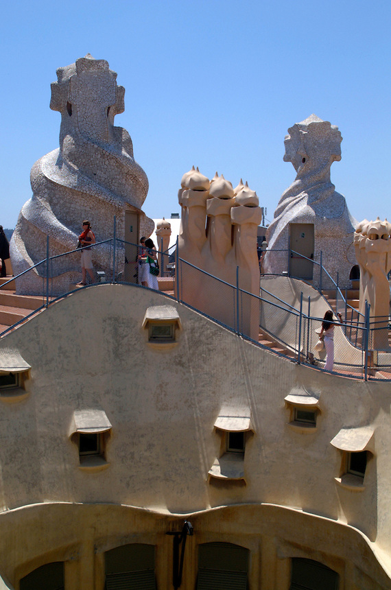 Sculpture and tourists on the rooftop of La Pedrera, one of Antoni Gaudi's apartment houses in Barcelona, Spain.