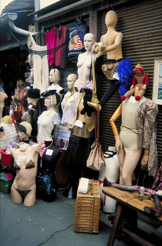 Clignancourt Flea Market with mannequins in various stages of undress, some with hat or purse. Lingerie and blouses. Wicker picnic basket. Doll with very long, skinny legs sits on low table straddling brass lamp base and bare bulb. Paris, France.