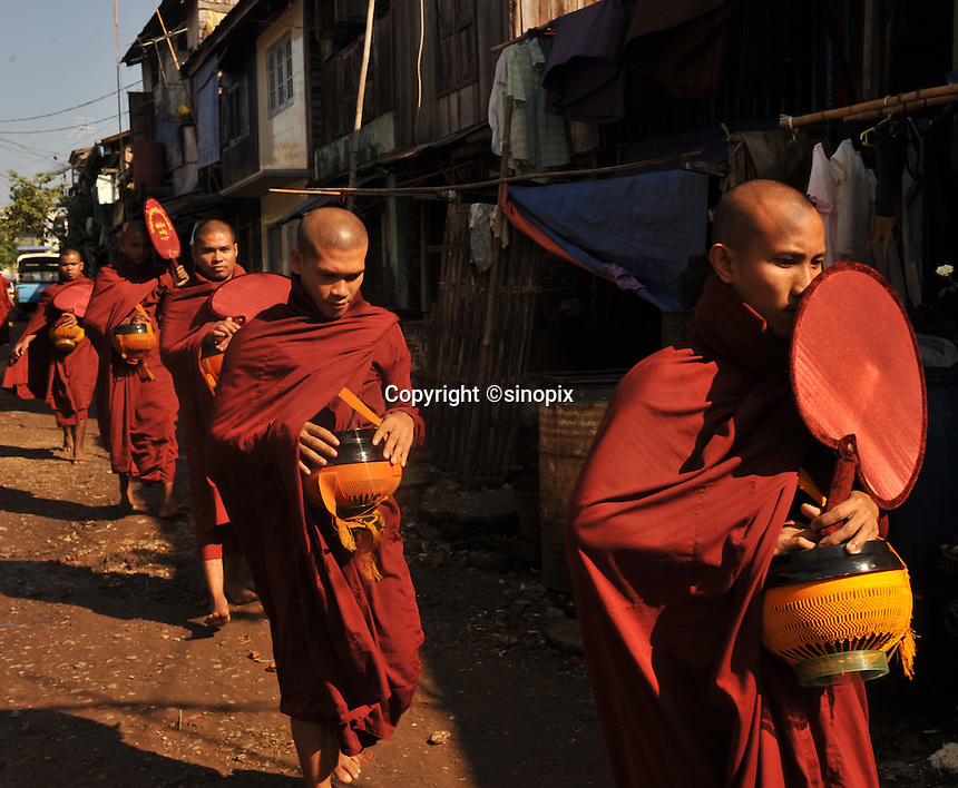 Monks walk through a village begging for a food in the centre of  Rangoon, Burma, NOV 2008.  Monks are given food by the population in this Buddhist country.<br /> <br /> Photo by Richard Jones