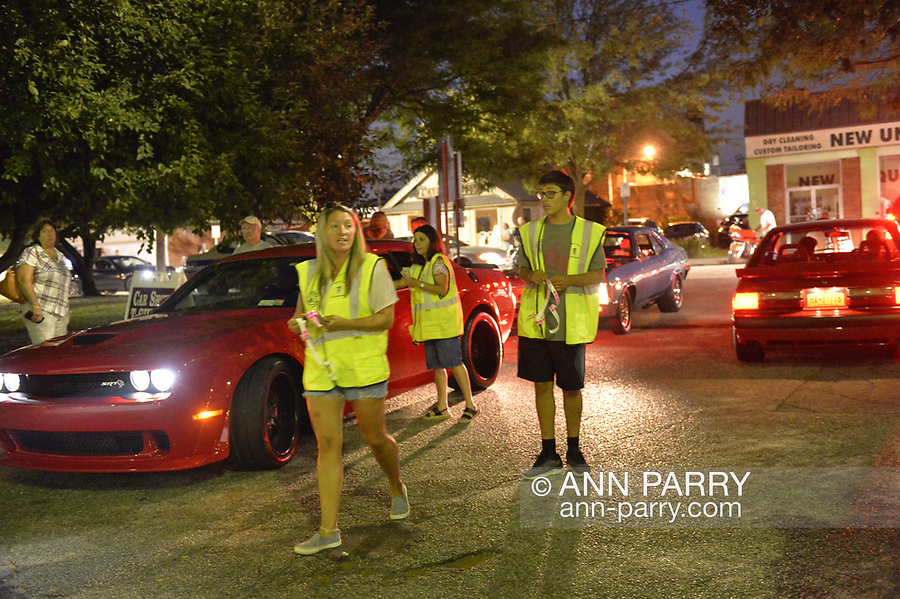 Bellmore, NY, USA. August 24, 2018. Members of Chamber of Commerce of the Bellmores, wearing yellow reflective safety vests, collect entrance fee from each car entering the Bellmore Friday Night Car Show. Visitors walk in for free.