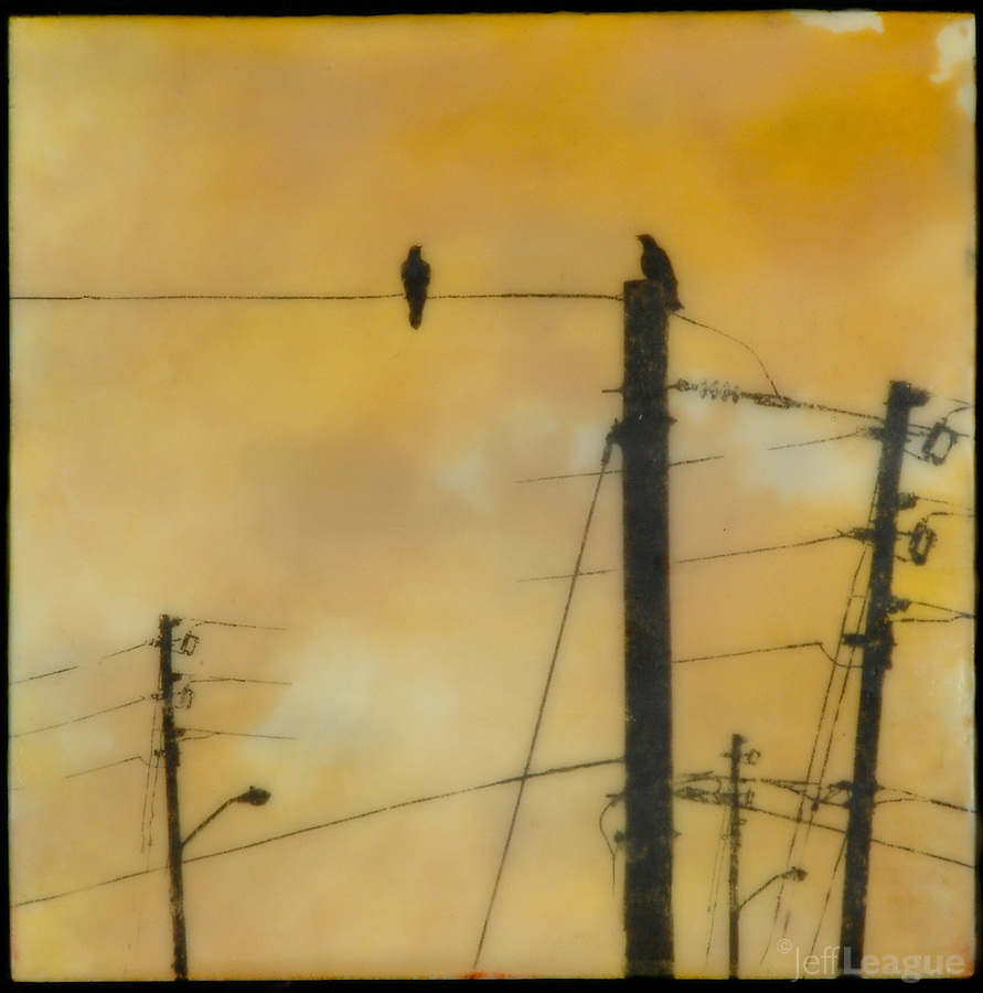 Mixed media encaustic painting with photography of crows on power lines in golden yellow.