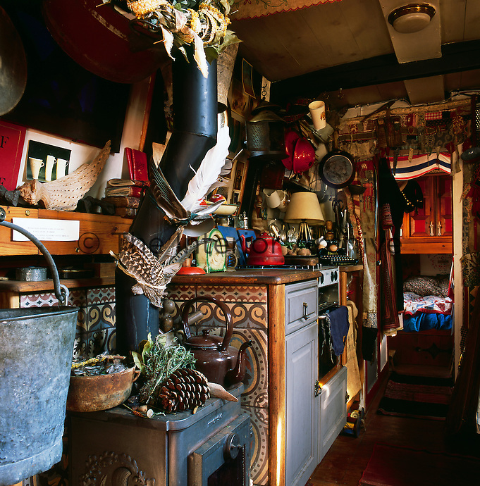 The cosy interior of a canal boat decorated in a bohemian style. The kitchen area with a view through to the sleeping cabin is heated by a wood-burning stove