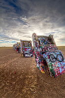 Cadillac Ranch is a public art installation and sculpture in Amarillo, Texas, U.S. It was created in 1974 by Chip Lord, Hudson Marquez and Doug Michels, who were a part of the art group Ant Farm, and it consists of what were (when originally installed during 1974) either older running used or junk Cadillac automobiles, representing a number of evolutions of the car line (most notably the birth and death of the defining feature of early Cadillacs; the tail fin) from 1949 to 1963, half-buried nose-first in the ground, at an angle corresponding to that of the Great Pyramid of Giza in Egypt.<br /> <br /> It was originally located in a wheat field, but in 1997 the installation was quietly moved by a local contractor two to the west, to a cow pasture along Interstate 40, in order to place it further from the limits of the growing city.<br /> <br /> Cadillac Ranch is visible from the highway, and though it is located on private land, visiting it (by driving along a frontage road and entering the pasture by walking through an unlocked gate) is tacitly encouraged. In addition, writing graffiti on or otherwise spray-painting the vehicles is also encouraged, and the vehicles, which have long since lost their original colors, are wildly decorated.
