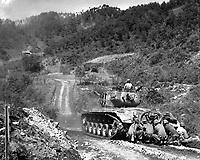 Marine infantrymen take cover behind a tank while it fires on Communist troops ahead.  Hongchon Area, May 22, 1951.  Sgt. John Babyak, Jr. (Marine Corps)<br /> NARA FILE #:  127-N-A8585<br /> WAR &amp; CONFLICT BOOK #:  1420