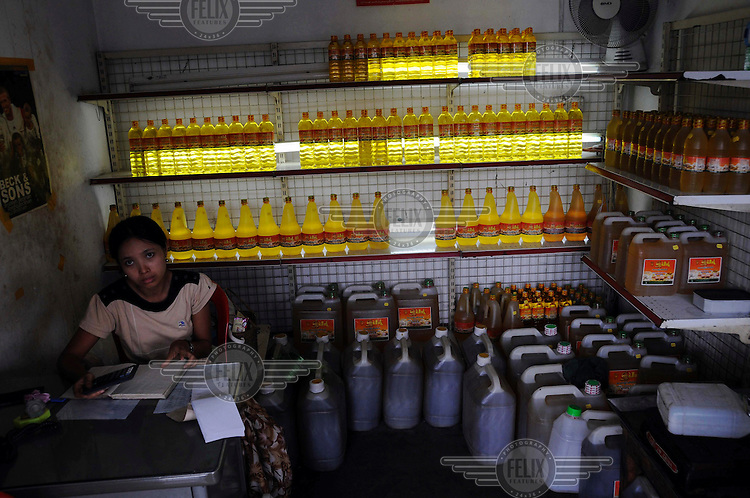 A cooking oil shop in a busy central market. There have been widespread rumours of foodstuffs donated for the cyclone relief effort being sold on by authorities (who administer most aid) to marketeers. Cyclone Nargis struck Burma on 02/05/2008.