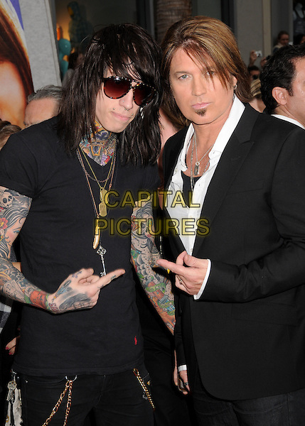 "TRACE CYRUS & BILLY RAY CYRUS .""Hannah Montana: The Movie"" Los Angeles Premiere held at the El Capitan Theatre, Hollywood, CA, USA, .2nd April 2009. .half length goatee beard facial hair necklaces tattoos hand gesture suit white shirt suit father son sunglasses goth .CAP/ADM/BP.©Byron Purvis/Admedia/Capital PIctures"