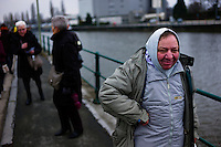 A man wearing a hood is seen the a canal in Halle, Belgium on March 10, 2013.