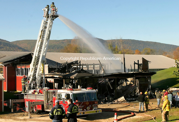 CANAAN, CT-08 OCTOBER 2006-100906JS01-Firefighters from Great Barrington, Mass. using their ladder truck, spray water on hot spots following an early morning fire at Elm Knoll Farm in Cannan on Monday. Firefighters from throughout the Northeast Corner and southwestern Massachuettes were called in to fight the blaze. -Jim Shannon Republican-American