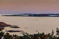 Människor vid havet på Järflotta med Landsorts fyr och horisonten av Östersjön.