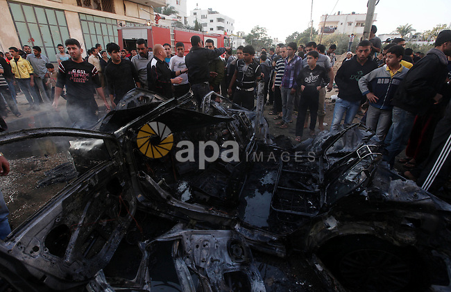 """Palestinian gather arround a destroyed car following an Israeli strike in Gaza City on November 20, 2012. Israel's air force dropped leaflets across several districts of Gaza City urging people to evacuate their homes """"immediately"""" amid fears of an imminent ground invasion. Photo by Majdi Fathi"""