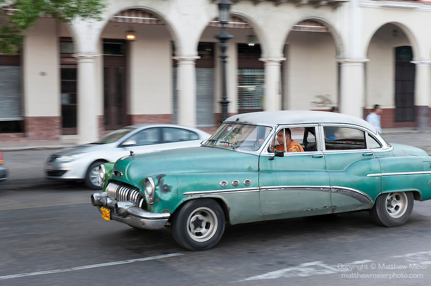 Havana, Cuba; a classic green and white 1951 Buick Super driving along the Paseo de Marti past the Saratoga Hotel
