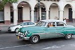 Havana, Cuba; a classic green and white 1951 Buick Super driving along the Paseo de Marti past the Saratoga Hotel