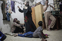 June 09, 2015 - Beirut, Lebanon: Widaad (centre) stands beside her husband Jamal (right bottom) as Jamal's brother, who suffers from a disability, lays on the ground at their room house in Shatila refugee camp. They are Syrian refugees from the city of Al Qusayr from where they fled four years ago when the fighting sparked out between opposition armed groups against loyalists to President Bashar Al-Assad. Left to the frame is pictured also Ammal Akkar and one of her daughters, both of them Palestinian refugees. (Photo/Narciso Contreras)