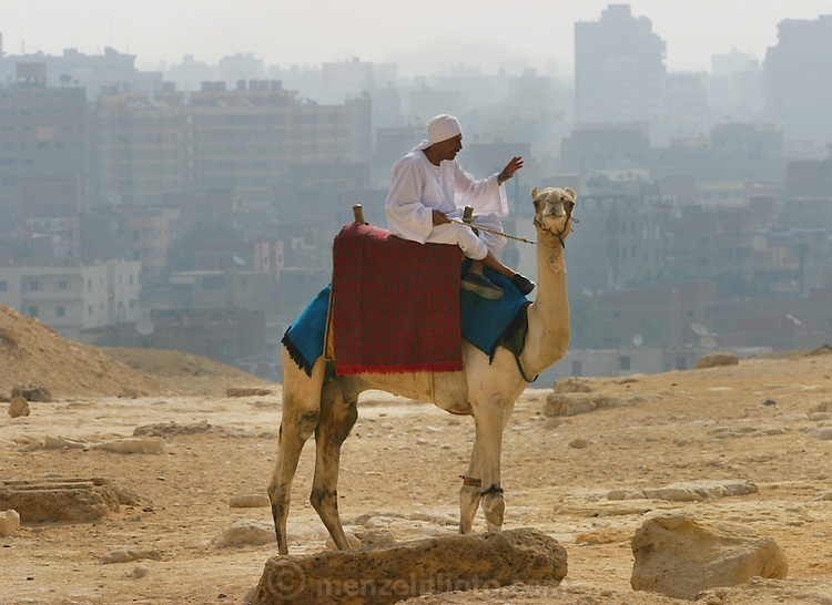 A camel riding guide looking for clients near the pyramids at Giza, outside Cairo, Egypt.
