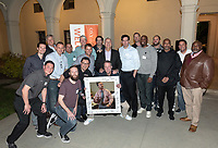 Newhall and 18 of his former players pose for photo in Booth Music Courtyard at a reception on January 26. Front row, l-r: Chase Young '03, Finn Rebassoo '03, Hung Duong '94 M'02, and Ethan Caldwell '90. Back row: nephew David Newhall '99, Hans Mumper '84, Jeff Muir '92, Michael Guzman '88, Scott Schroeder '85, Trevor Moawad '95 M'01, John Keister '89, Brian Newhall '83, John Pike '96, Ted Steben '99, Sandy Brown '93, Jason Muir '97 M'99, Michael Whaley '84, Tim Walsh '98, and Omar Anderson '95. <br /> Now in his 30th year as Oxy's head men's basketball coach, Brian Newhall received a much deserved celebration with a surprise halftime ceremony and post game reception in the Booth Hall courtyard with more than 70 former and current players from all different generations and decades in attendance, on Saturday, Jan. 26, 2019.<br /> Newhall is the winningest coach in Oxy history and has a 100 percent graduation rate in his 30 years at the helm of the program. His resume boasts multiple SCIAC Championships and NCAA Playoff appearances, along with a run to the NCAA Division III Elite Eight in 2003 and the only perfect 14-0 season in SCIAC history. Newhall has not only coached at Oxy, but was a SCIAC Champion and SCIAC Player of the Year during his playing career at Oxy in the early 80s.<br /> (Photo by Marc Campos, Occidental College Photographer)