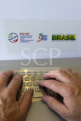 A man is typing on the keyboard of a dedicated information computer with a Rio+20 sticker and a Brazil governmnet sticker. United Nations Conference on Sustainable Development (Rio+20), Rio de Janeiro, Brazil.