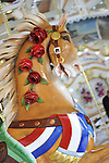 Carousel horse at historic Nunley's Carousel Centennial Celebration on Saturday, June 9, 2012, at Museum Row, Garden City, Long Island, New York, USA. 100th Anniversary festivities included old time game of croquet; a visit from ex-President Theodore Roosevelt - portrayed by actor James Foote - who ran again for President in 1912 (unsuccessfully, as Bull Moose Party candidate), the year Nunley's Carousel debuted; and Carousel rides. Horse has red white and blue sash and roses along mane.