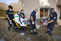 Switzerland. Canton Ticino. Mezzovico. A senior man is carried seated on chair, then by ambulance to the hospital for medical examinations. The elderly man is suffering from severe respiratory problems. The emergency doctor Daniele Speciale (R) is working with three paramedics. They all work for the Croce Verde Lugano. They wear blue uniforms, medical gloves and surgical masks. The man and the woman (L) are professional certified nurses, the bald man (C) is a volunteer specifically trained in emergency rescue. The senior citizen has a mask on his face and receives oxygen from a medical ventilator carried by the doctor. A medical ventilator (or simply ventilator in context) is a mechanical ventilator, a machine designed to move breathable air into and out of the lungs, to provide breathing for a patient who is physically unable to breathe, or breathing insufficiently. The Croce Verde Lugano is a private organization which ensure health safety by addressing different emergencies services and rescue services. Volunteering is generally considered an altruistic activity where an individual provides services for no financial or social gain to benefit another person, group or organization. Volunteering is also renowned for skill development and is often intended to promote goodness or to improve human quality of life. Medical gloves are made of different polymers including latex, nitrile rubber, polyvinyl chloride and neoprene. 14.01.2018 © 2018 Didier Ruef