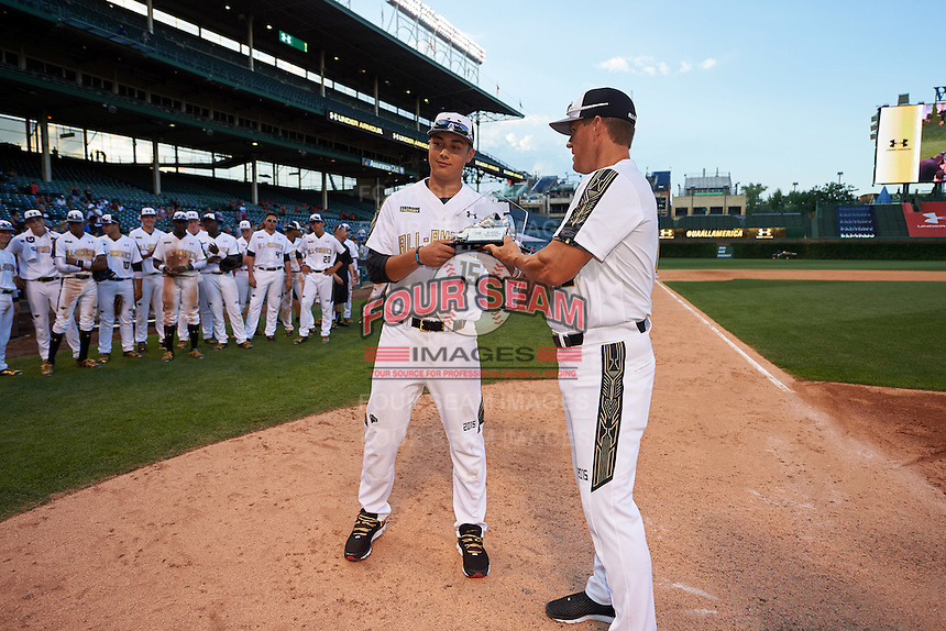 Andy Yerzy (15) of York Mills Collegiate Institute in Toronto, Ontario is presented with his teams Most Valuable Player Award by Wes Helms (18) after the Under Armour All-American Game on August 15, 2015 at Wrigley Field in Chicago, Illinois. (Mike Janes/Four Seam Images)