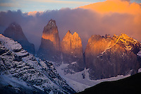 The famous towers of Torres Del Paine, Patagonia Chile glow red as the first rays of the sun break the horizon.