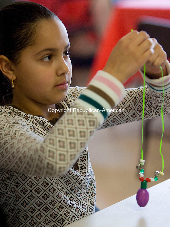 WATERBURY, CT - 12 DECEMBER 2009 -121209JT11--<br /> Jalysa Perez, 11, makes a Christmas ornament necklace at the River Baldwin Recreation Center in Waterbury on Saturday morning during a free breakfast and a visit from Santa hosted by the South End Neighborhood Association. <br /> Josalee Thrift Republican-American